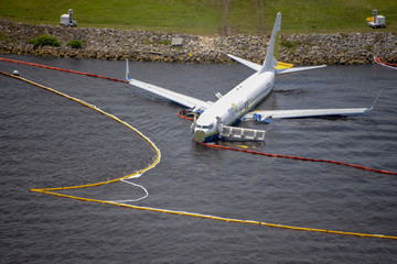 Containment and absorbent booms surround a Boeing 737 aircraft in the St. Johns River after the aircraft slid off the runway at Naval Air Station, Jacksonville, Florida