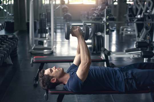 Handsome weightlifter lifting bench press working out with dumbbell in the gym