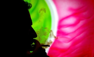 A man is silhouetted as he smokes a cigarette inside a bar in Rome.