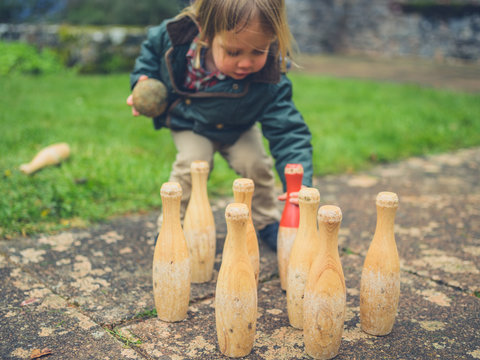 Little toddler setting up bowling pins outdoors