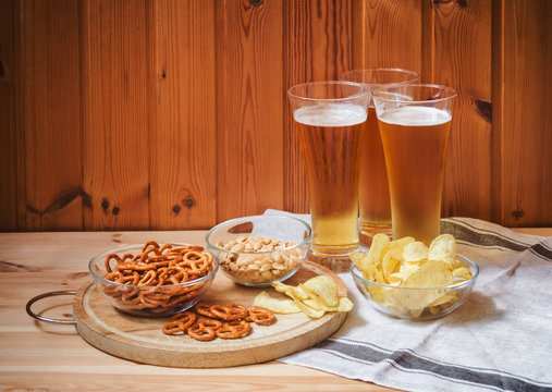 Light  beer with salted pretzels, potato chips and peanuts on  wooden table. Selective focus.
