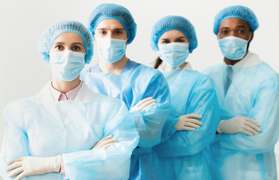 Surgeons Team Wearing Protective Uniforms, Standing In Row
