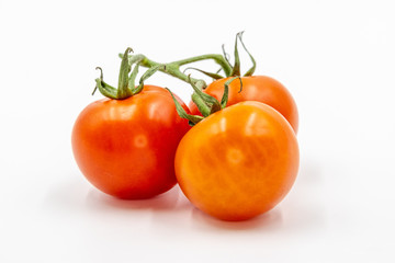 Three red tomatoes with branch