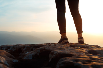 Unrecognizable young success woman hiker legs on mountain peak rock, rear view.  Concept achieving goal, beginning of the path, travel,  adventure, sport