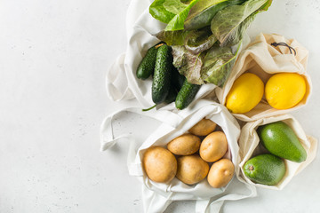 Zero waste concept. Textile ecologiical shopping bags with fruits and vegetables on white background