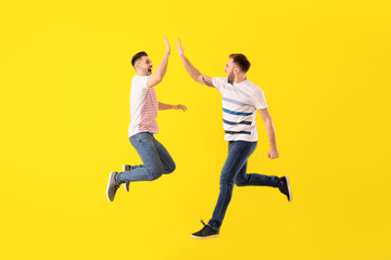 Jumping young men on color background Fototapete