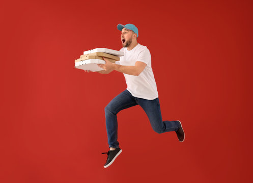 Jumping male courier with pizza boxes on color background