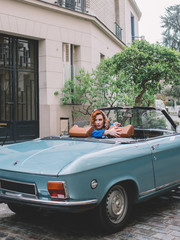 Glamourous woman driving a vintage car in Paris, retro style