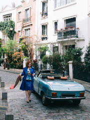 Glamorous woman walking in Paris next to a vintage car, retro style
