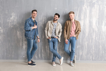 Fashionable young men near grey wall Wall mural