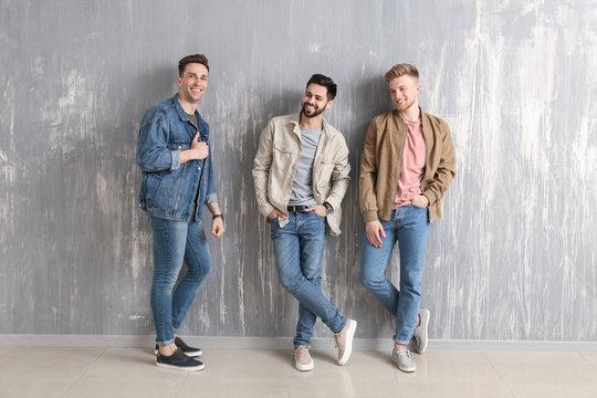 Fashionable young men near grey wall