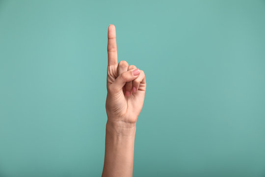 Gesturing female hand on color background