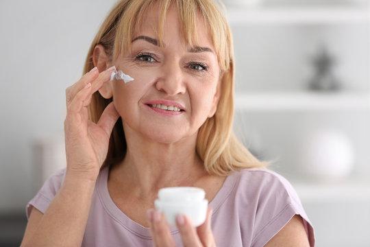 Mature woman applying facial cream at home