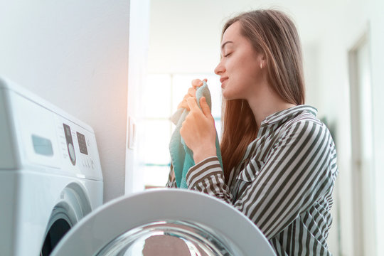 Beautiful young woman smelling and enjoying the scent of fresh clean towel after laundry at home