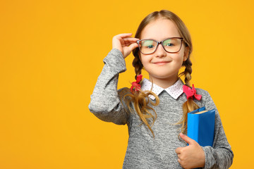 Portrait of a cute little kid girl on a yellow background. Child schoolgirl looking at the camera,...