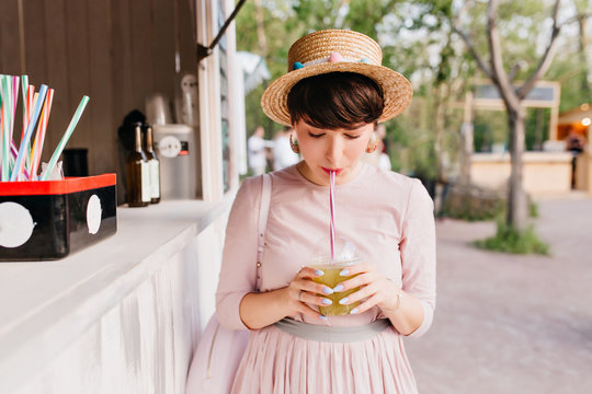 Cute short-haired young lady with elegant purple manicure drinking green cocktail standing near the snack-bar. Portrait of charming brunette girl enjoying juice with eyes closed in morning.