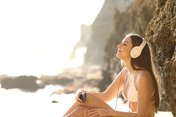 Relaxed sunbather listens to music on the beach