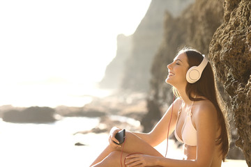 Relaxed tourist in bikini listening to music on the beach