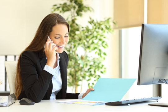 Office worker checking document talking on phone