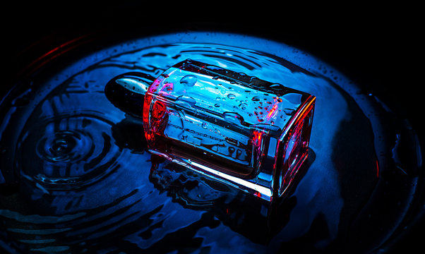glass of perfume on water background