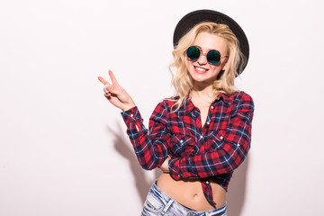 Smiling blonde woman in checkered shirt and hat showing peace gestures and looking at the camera over white background