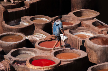 Blurred image of factory Tanneries of Fes, old big tanks of the Fez's tanneries with workers who working in a tannery on traditional craft leather dying. Morocco, Africa