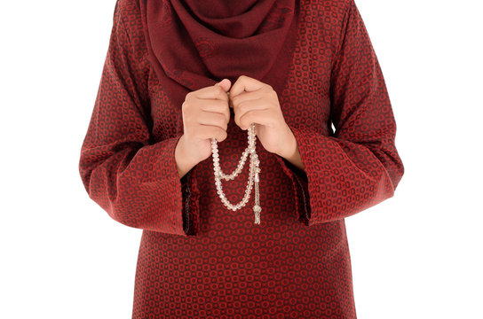 Young muslim woman holding a rosery or tasbih with isolated on white background