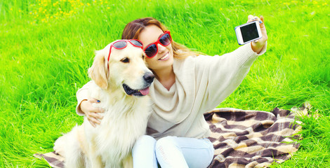 Happy smiling woman with Golden Retriever dog taking selfie picture by phone in summer day