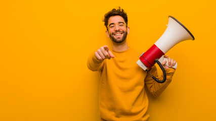 Young man holding a megaphone cheerful and smiling