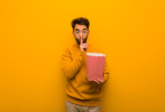 Young man holding popcorns keeping a secret or asking for silence