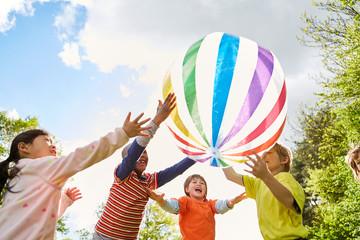 Kinder im Kindergarten beim Ballspiel im Park