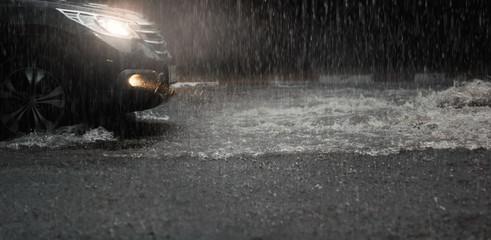 Car with headlights run through flood water after hard rain fall at night. Fototapete