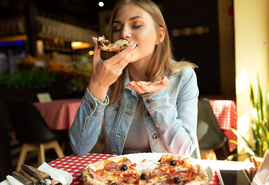 Funny blonde girl in jeans jacket eating pizza at restaurant.