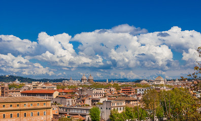 Rome historic center old skyline above Trastevere with old churches, belltowers, domes and clouds, seen from Aventine Hill