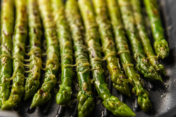 asparagus sprinkled with parmesan cheese fried in a pan