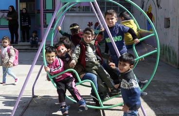 Children play on a swing at a preschool in Qamishli