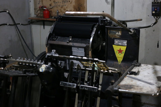 YPG logo is seen on a machine at a printing press in Qamishli