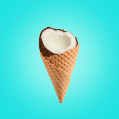 Coconut with ice cream cone on bright background. Food minimal concept.