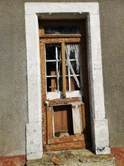 Old rotten entrance door to an abandoned house