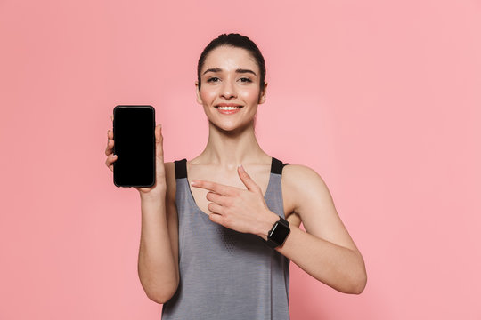 Amazing beautiful young pretty fitness woman showing display of mobile phone isolated over pink wall background.