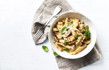 Penne pasta with mushrooms, chicken and cream sauce. Mediterranean cuisine. Flat lay. White background