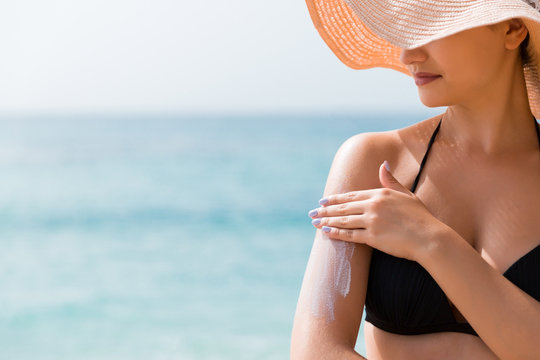 Sunscreen sunblock. Woman in a hat putting solar cream on shoulder outdoors under sunshine on beautiful summer day