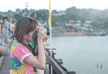 Cute girl taking pictures on a wooden bridge in the air, glowing bright sky.
