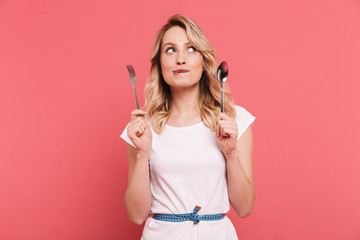Portrait of thoughtful blond woman 20s wearing body measuring tape around waist holding spoon and fork
