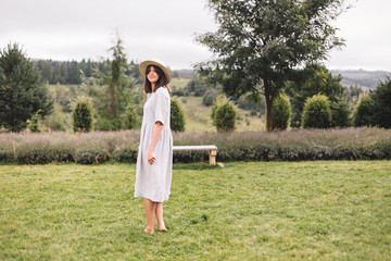Stylish hipster girl in linen dress and hat walking at lavender field and relaxing in mountains....