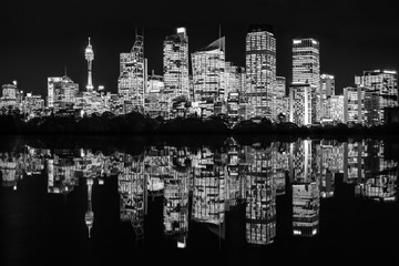 Beautiful Sydney Waterfront Skyline at Night in black and white with reflections in the bay in New South Wales, Australia.
