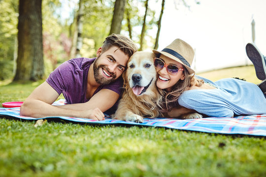 Young couple having picnic with their dog in the park, lying on blanket and looking at camera