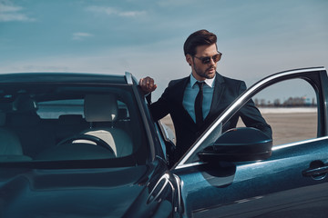 Luxury style. Handsome young businessman entering his car while standing outdoors Wall mural