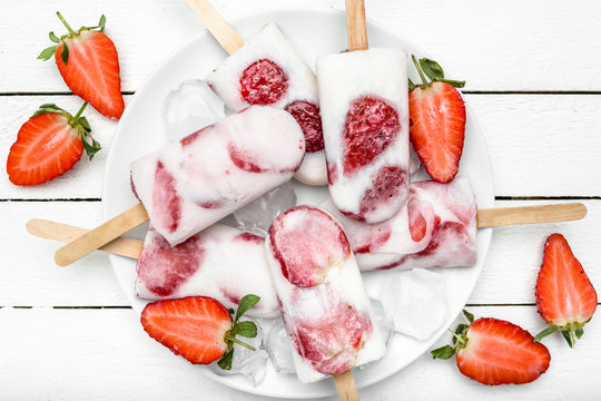 Fresh strawberry popsicles with yogurt and fruits, ice cream frozen on sticks