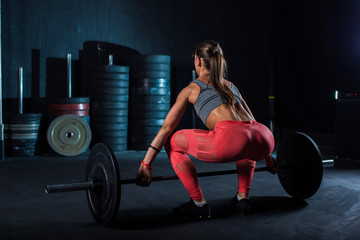 Young, European, muscular girl in red leggings, doing exercise with a barbell in the gym for crossfit. Dark background Wall mural